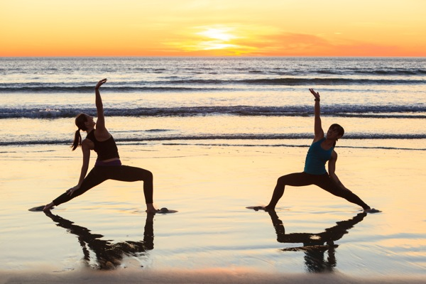 Women practicing Yoga reflected in wet sand on Pacific Beach at sunset, San Diego, California, USA © Stuart Westmorland/evolveimages.com